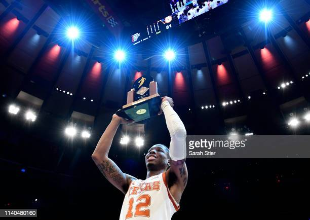 Kerwin Roach II of the Texas Longhorns raises the Most Outstanding Player trophy after the Texas Longhorns defeat the Lipscomb Bisons 8166 in the NIT...
