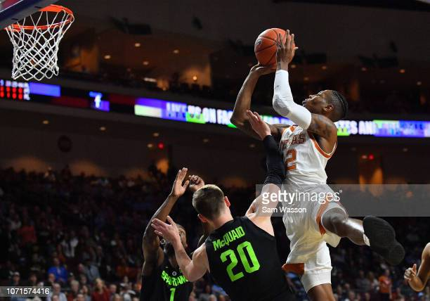 Kerwin Roach II of the Texas Longhorns shoots against Joshua Langford and Matt McQuaid of the Michigan State Spartans during the championship game of...