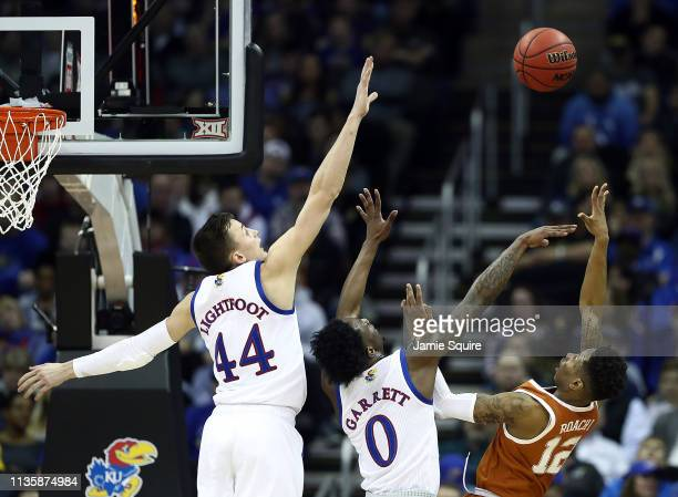 Kerwin Roach II of the Texas Longhorns shoots over Marcus Garrett and Mitch Lightfoot of the Kansas Jayhawks during the quarterfinal game of the Big...