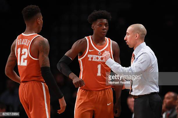 Kerwin Roach Jr #12 and Andrew Jones of the Texas Longhorns talk with head coach Shaka Smart during a timeout against the Northwestern Wildcats in...