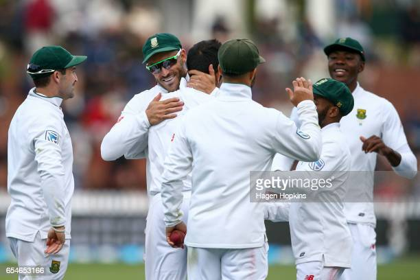 Keshav Maharaj of South Africa celebrates with captain Faf du Plessis after taking the wicket of Jeetan Patel of New Zealand to secure his 5 wicket...