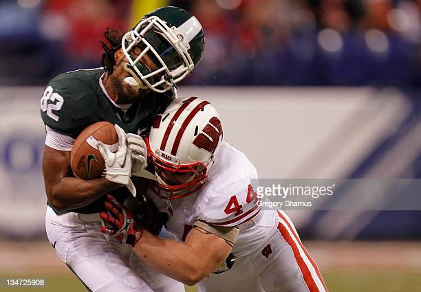 Keshawn Martin of the Michigan State Spartans loses his helmet as he is hit by Chris Borland of the Wisconsin Badgers during the third quarter of the...