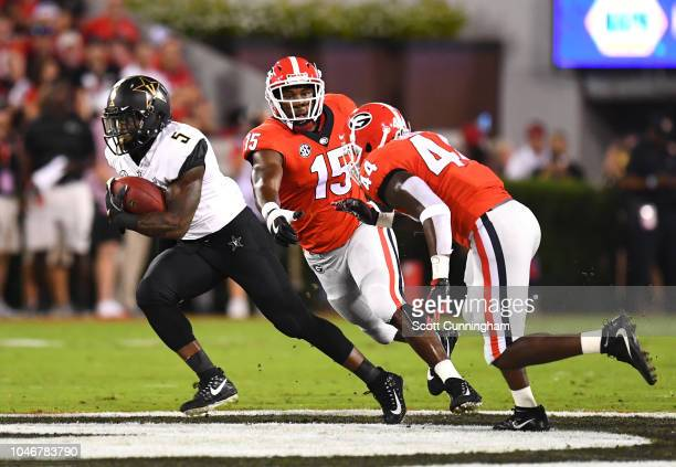 KeShawn Vaughn of the Vanderbilt Commodores carries the ball against Juwon Taylor and DAndre Walker of the Georgia Bulldogs on October 6 2018 at...
