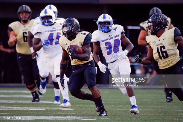 Ke'Shawn Vaughn of the Vanderbilt Commodores runs past Blair Edwards and Dell Porter of the Tennessee State Tigers to score a touchdown during the...