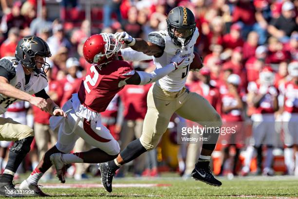 Ke'Shawn Vaughn of the Vanderbilt Commodores runs the ball and stiff arms Kamren Curl of the Arkansas Razorbacks in the second half at Razorback...