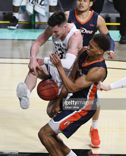 Kessler Edwards of the Pepperdine Waves fouls Alex Barcello of the Brigham Young Cougars during the West Coast Conference basketball tournament...