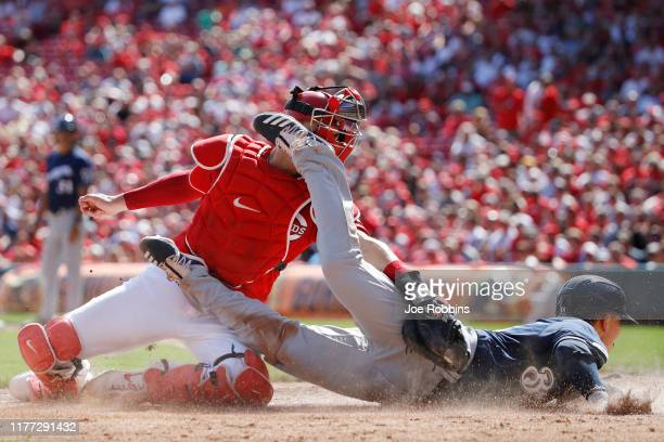 Keston Hiura of the Milwaukee Brewers kicks Curt Casali of the Cincinnati Reds in his facemask while getting tagged out trying to score in the fifth...