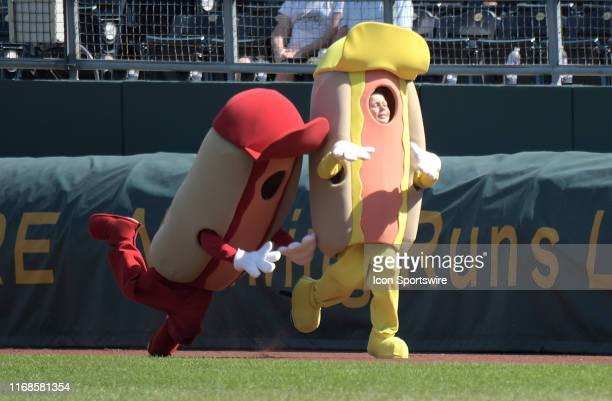 Ketchup falls down as Mustard pulls ahead in the Hotdog Race during a Major League Baseball game between the Houston Astros and the Kansas City...