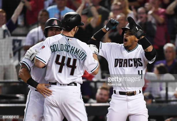 Ketel Marte and David Peralta of the Arizona Diamondbacks congratulate Paul Goldschmidt after he hit a three run home run in the first inning of the...