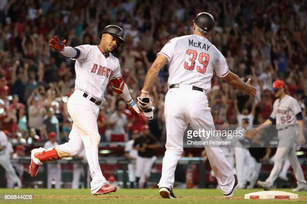 Ketel Marte of the Arizona Diamondbacks celebrates with first base coach Dave McKay after hitting the game winning RBI single against the Colorado...