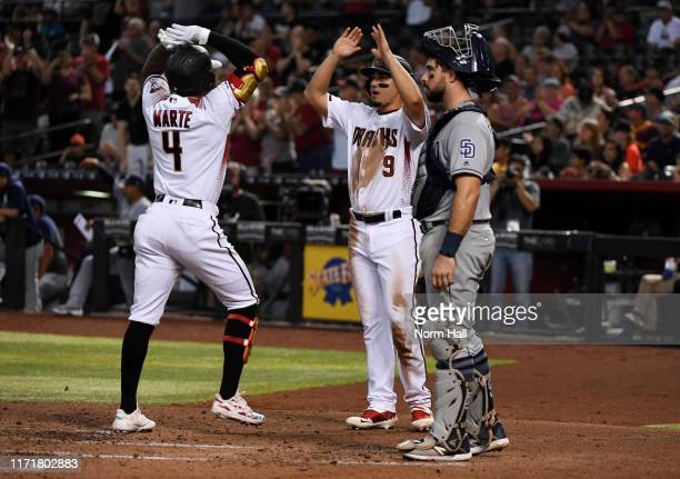 Ketel Marte of the Arizona Diamondbacks celebrates with Josh Rojas after hitting a two run home run off of Cal Quantrill of the San Diego Padres...