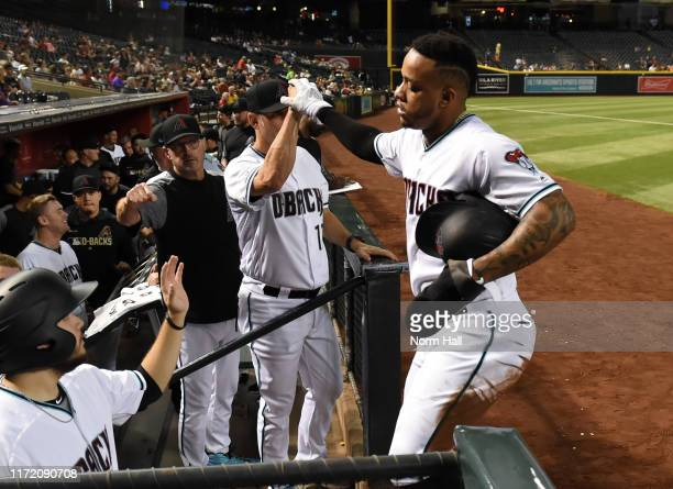 Ketel Marte of the Arizona Diamondbacks celebrates with manager Torey Lovullo after scoring on a single by Josh Rojas during the first inning against...