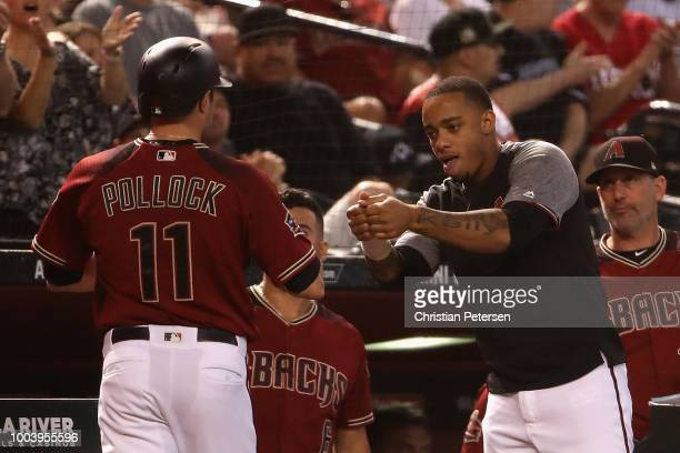 Ketel Marte of the Arizona Diamondbacks congratulates AJ Pollock after scoring against the Colorado Rockies during the first inning of the MLB game...