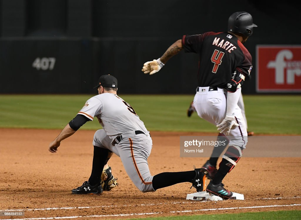 Ketel Marte #4 of the Arizona Diamondbacks grabs the back of his right leg while crossing first base as Brandon Belt #9 of the San Francisco Giants scoops a throw out of the dirt for a force out during the seventh inning at Chase Field on June 30, 2018 in Phoenix, Arizona.