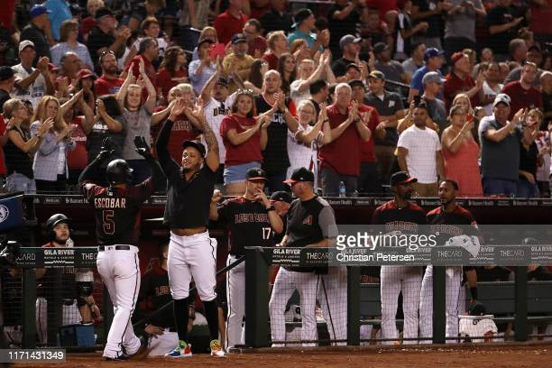 Ketel Marte of the Arizona Diamondbacks high fives Eduardo Escobar after Escobar hit a solo home run against the Los Angeles Dodgers during the...