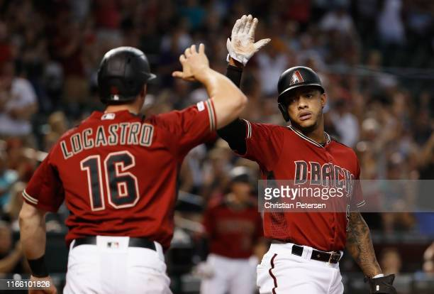 Ketel Marte of the Arizona Diamondbacks high fives Tim Locastro after both scored runs against the Washington Nationals during seventh inning of the...