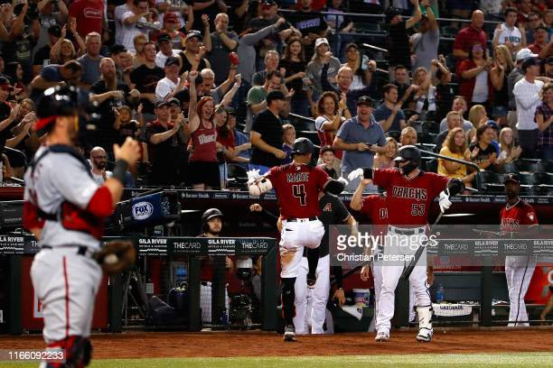 Ketel Marte of the Arizona Diamondbacks is congratulated by Christian Walker after Marte hit an inside the park home run against the Washington...
