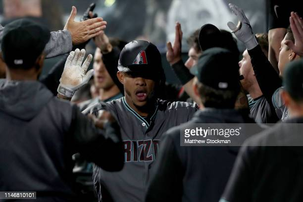Ketel Marte of the Arizona Diamondbacks is congratulated on the dugout after scoring on an Eduardo Escobar 2 RBI home run in the fifth inning against...