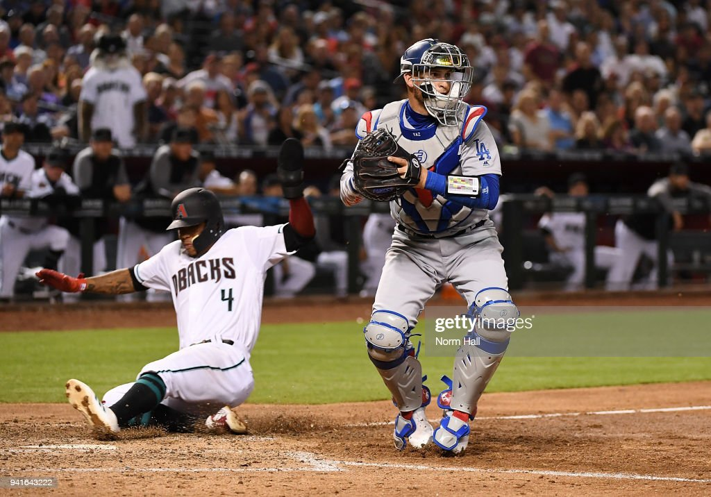 Ketel Marte #4 of the Arizona Diamondbacks is forced out at home plate during the seventh inning Yasmani Grandal #9 of the Los Angeles Dodgers looks to throw the ball to first base at Chase Field on April 3, 2018 in Phoenix, Arizona.
