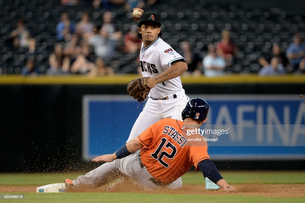 Ketel Marte #4 of the Arizona Diamondbacks turns a double play over the sliding Max Stassi #12 of the Houston Astros in the seventh inning at Chase Field on August 15, 2017 in Phoenix, Arizona.