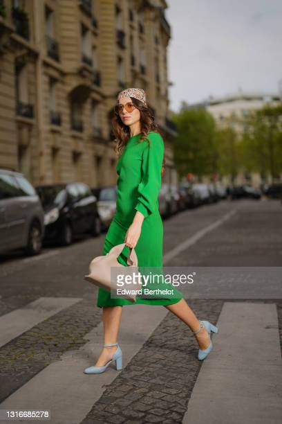 Ketevan Giorgadze @katie.one wears a midi green dress with a round neckline, long gathered sleeves, from Zara, a beige leather drape form bag from...