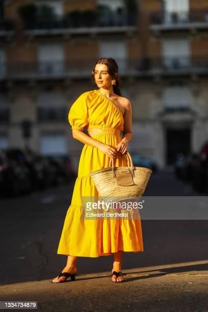 Ketevan Giorgadze @katie.one wears a one shoulder cut out maxi dress in orange from Mango, oversized golden hoop earrings from Zara, flip flop heeled...