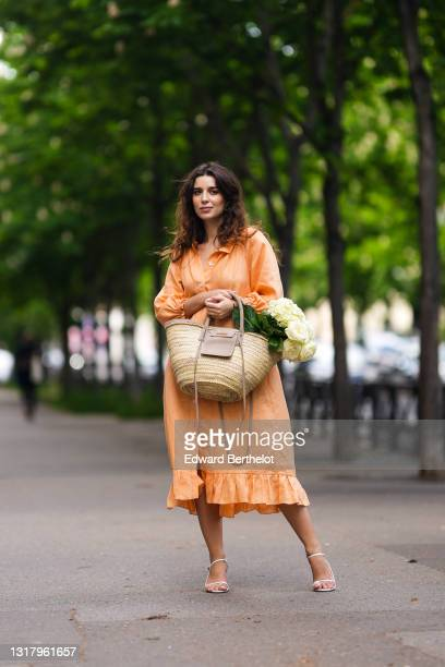 Ketevan Giorgadze @katie.one wears gold earrings, a long buttoned coral loungewear linen The Sleeper dress with puffy sleeves, gold rings, a wicker...