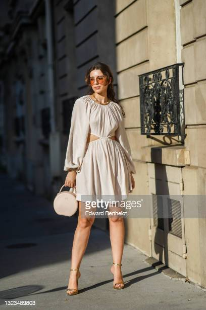 Ketevan Giorgadze @katie.one wears oversized sunglasses by For Art's Sake, a gold chain necklace by For Art's Sake, a white cut out mini dress with...