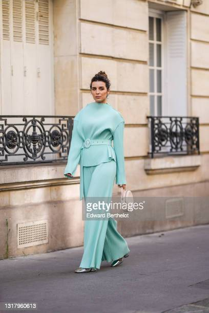 Ketevan Giorgadze @katie.one wears silver earrings, a pale blue oversized belted chiffon lightweight handmade plissé / ribbed long sleeves top with...
