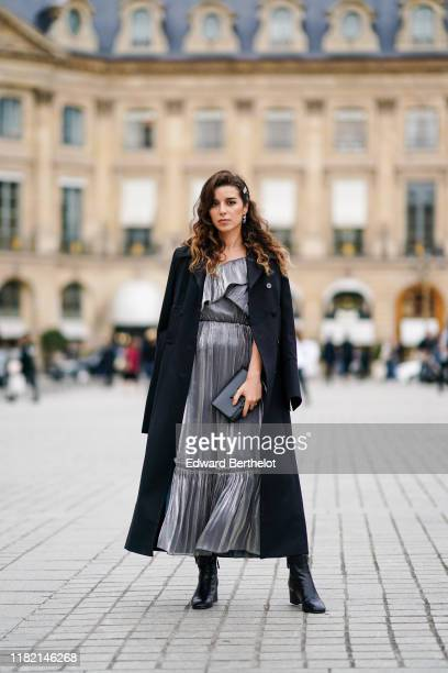 Ketevan Giorgadze wears a hair clip, earrings, a shiny ruffled grey dress with grey polka dots, a black coat, a black clutch, black ankle-boots,...