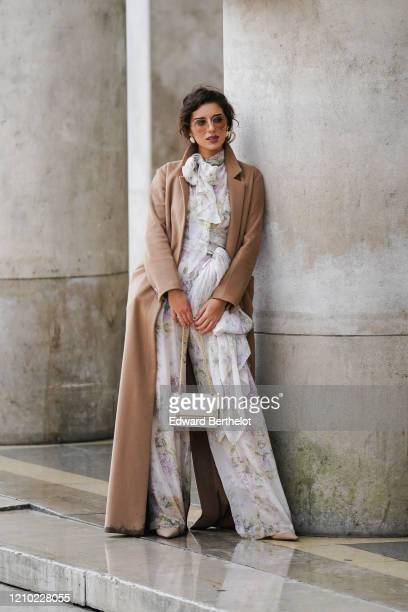 Ketevan Giorgadze wears sunglasses, earrings, a camel long coat, a white flowing jumpsuit with colorful floral prints, a lavaliere and a belt bow,...