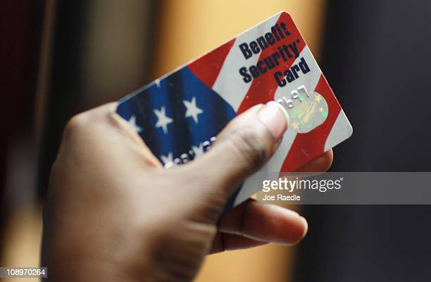 Kethia Dorelus a social worker with the Cooperative Feeding Program displays a Federal food stamps card that is used to purchase food on February 10...