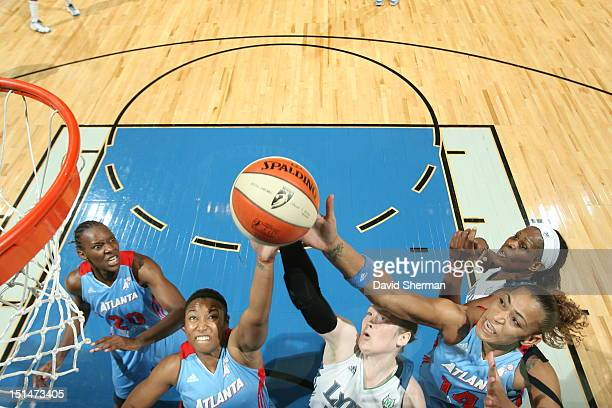 Ketia Swanier and Erika de Souza of the Atlanta Dream fight for the rebound against Lindsay Whalen of the Minnesota Lynx during the WNBA game on...