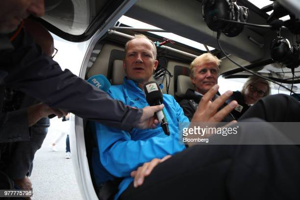 Ketil SolvikOlsen Norway's transport minister left speaks to a journalist as he sits in the cockpit of an Avinor AS Alpha Electro G2 electric...