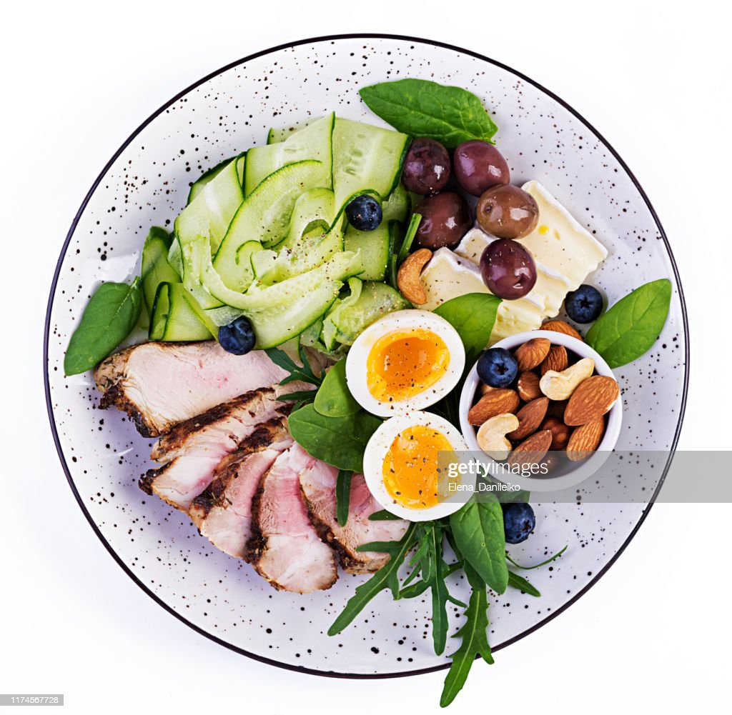 Ketogenic diet. Keto brunch. Boiled egg, pork steak and olives, cucumber, spinach, brie cheese, nuts and blueberry. Top view : Stock Photo