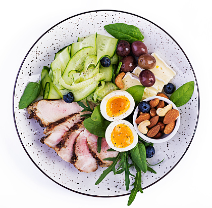 Ketogenic diet. Keto brunch. Boiled egg, pork steak and olives, cucumber, spinach, brie cheese, nuts and blueberry. Top view 1174567728