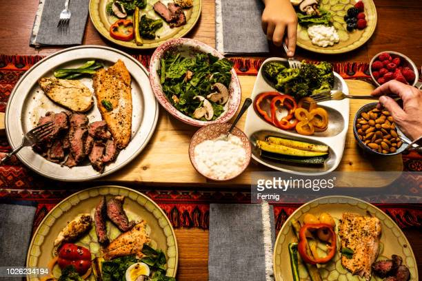 a ketogenic meal laid out on a dining table with the hands of people serving themselves - fat nutrient stock pictures, royalty-free photos & images
