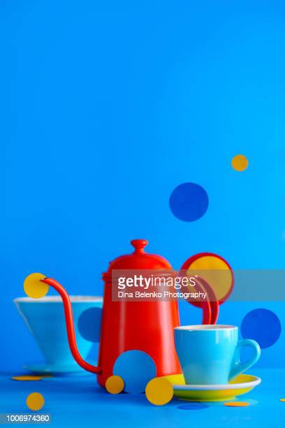 kettle and porcelain coffee cups on a vibrant blue background. color block coffee equipment still life. geometry and color in food photography. suprematic concept with copy space - red kettle stock photos and pictures