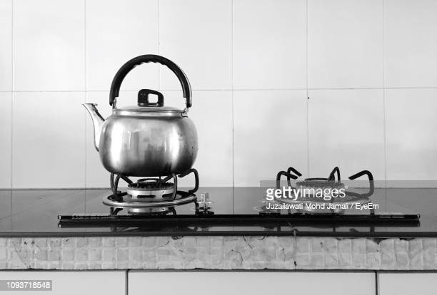 kettle and stove against wall on counter in kitchen - placa de fogão - fotografias e filmes do acervo