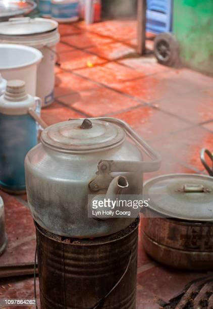 kettle boiling in street - lyn holly coorg stockfoto's en -beelden