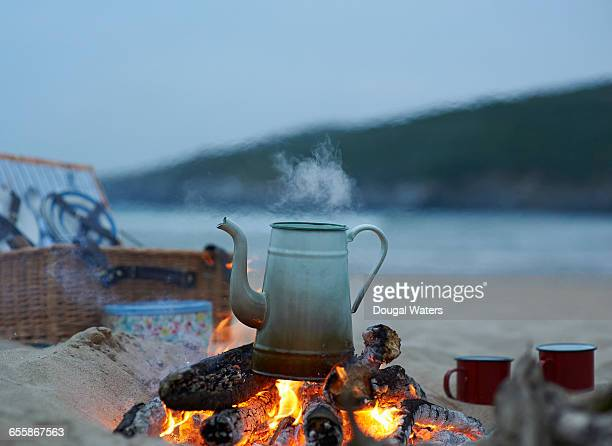 kettle boiling on campfire at beach. - dougal waters stock pictures, royalty-free photos & images