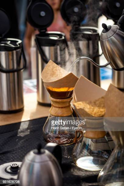 Kettle Pouring Water Through Filter In Coffee