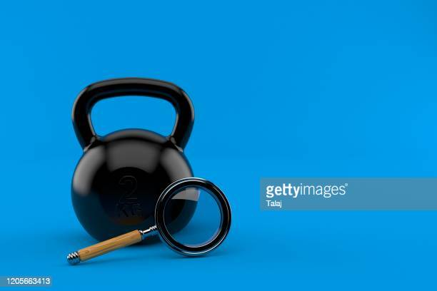 kettlebell with magnifying glass isolated blue