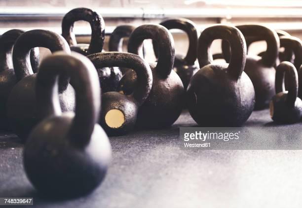 kettlebells on floor in gym - sportgerät stock-fotos und bilder
