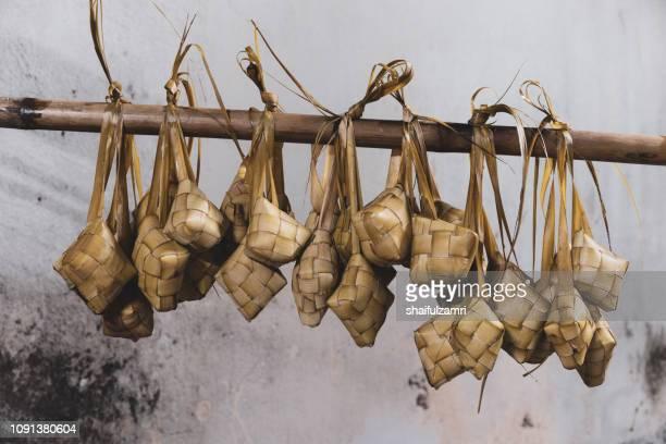 ketupat - a traditional food hanging on bamboo. - shaifulzamri stockfoto's en -beelden