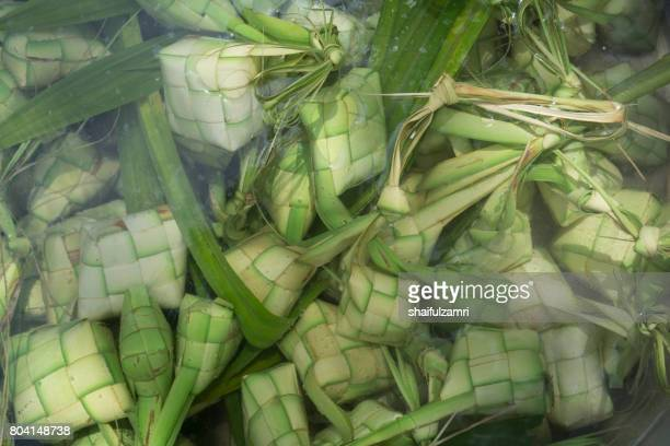 ketupat, kupat or tipat is a type of dumpling made from rice packed inside a diamond-shaped container of woven palm leaf pouch. it is commonly found in indonesia, malaysia, brunei and singapore. - shaifulzamri stock-fotos und bilder