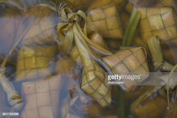 ketupat, kupat or tipat is a type of dumpling made from rice packed inside a diamond-shaped container of woven palm leaf pouch. it is commonly found in indonesia, malaysia, brunei and singapore. - shaifulzamri stock pictures, royalty-free photos & images