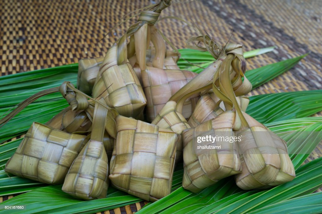 Ketupat, Kupat or Tipat is a type of dumpling made from rice packed inside a diamond-shaped container of woven palm leaf pouch. It is commonly found in Indonesia, Malaysia, Brunei and Singapore. : Stock Photo