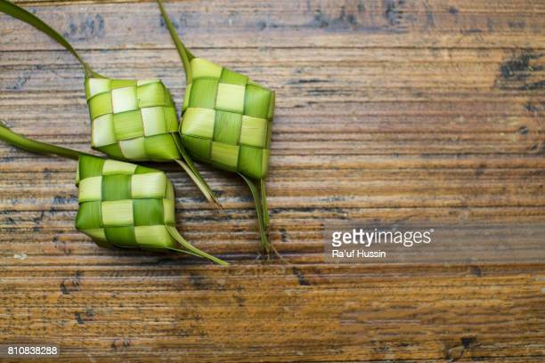 ketupat or rice dumpling on wooden background - hari raya stock pictures, royalty-free photos & images