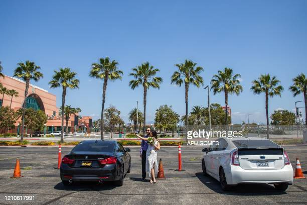 TOPSHOT Kev and Tiffany McCaryan pose for a selfie after being married by a clerk recorder at the Honda Center parking lot on April 21 2020 in...